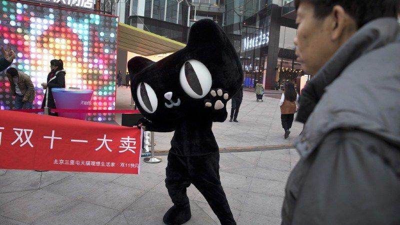 """Dans une rue de Pékin, la mascotte d'un site d'achat en ligne brandit une bannière avec le mot """"Double 11 grande vente"""" lors d'un événement promotionnel de la """"Journée des célibataires""""."""